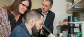 Patrick McDonough looks at rare cancer cells grown in the lab of Nabeel Bardeesy, PhD, (at right) as Patrick's mother Ann Marie McDonough looks on.
