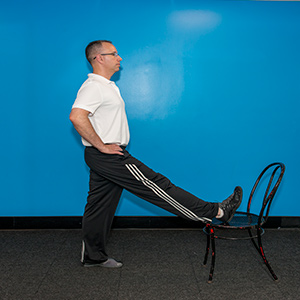 Stretch the back of the thigh by elevating your leg on chair and flexing foot.
