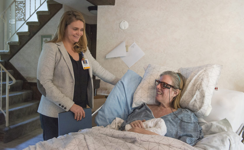 Mass General ALS nurse Katie Tee, RN (left), speaks with patient Linda Hank during a house call visit. The device on Ms. Hank's glasses is an eye-tracker which is linked to a tablet and allows her to type and speak without using her hands or voice.