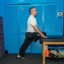 Regular stretching can help older adults feel better. This move stretches the back of the hip of the elevated leg.