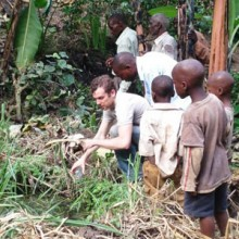 Ross Boyce, MD, MSc, (left), accompanied by local residents near Bugoye, Uganda, as he collects samples for malaria research.