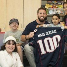 Dane Fletcher of the New England Patriots with young patients at MassGeneral Hospital for Children.