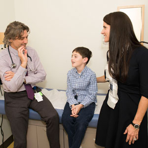 Nine-year-old Michael and his mother Jean Egan check in with Dr. Alessio Fasano, left.