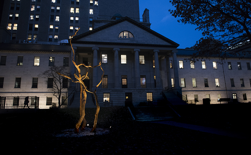 "Pictured at night, the artwork titled ""Open Arms"" was created by philanthropist Harold Grinspoon, whose sculptures are made from fallen trees."