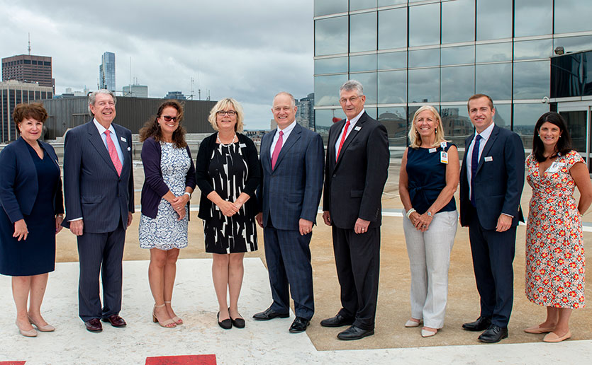 Leaders from John Hancock and Mass General gather at the Emergency Department helipad to celebrate their ongoing partnership. (The names of those photographed appear at end of story.)