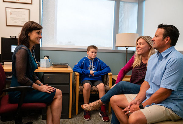Janet Wozniak, MD, has an annual check-in with Jett and his parents.