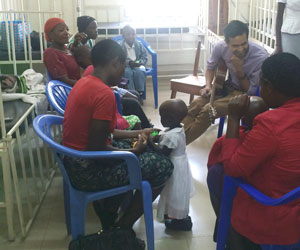 Mass General music therapist Julio Gudino (top right) works with children and parents at the Mbarara Regional Referral Hospital.