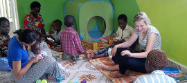 Maggie Berry (at right) participates in the art and music therapy program she founded for children in a cancer clinic in Uganda.