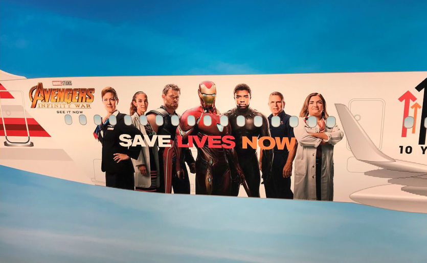 "A custom-wrapped American Airlines plane features Mass General researcher Marcela Maus, MD, PhD (right), alongside superheroes Thor, Iron Man and Black Panther from the movie, ""Avengers: Infinity War."""