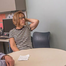 Christopher McDougle, MD, (left) director of the Lurie Center for Autism, checks in with Alex Saffron and his mother.
