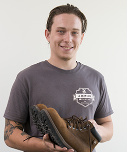 Billy Morrissey with boots his mother donated to the bridge clinic.