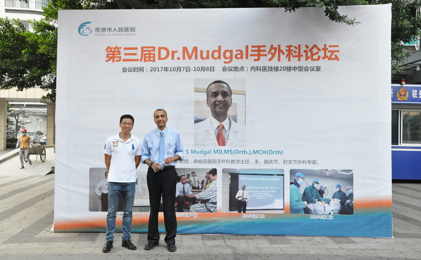 Mass General surgeon Chaitanya Mudgal, MD, right, and an attendee in front of a sign announcing Dr. Mudgal's conference in Guigang City, China.