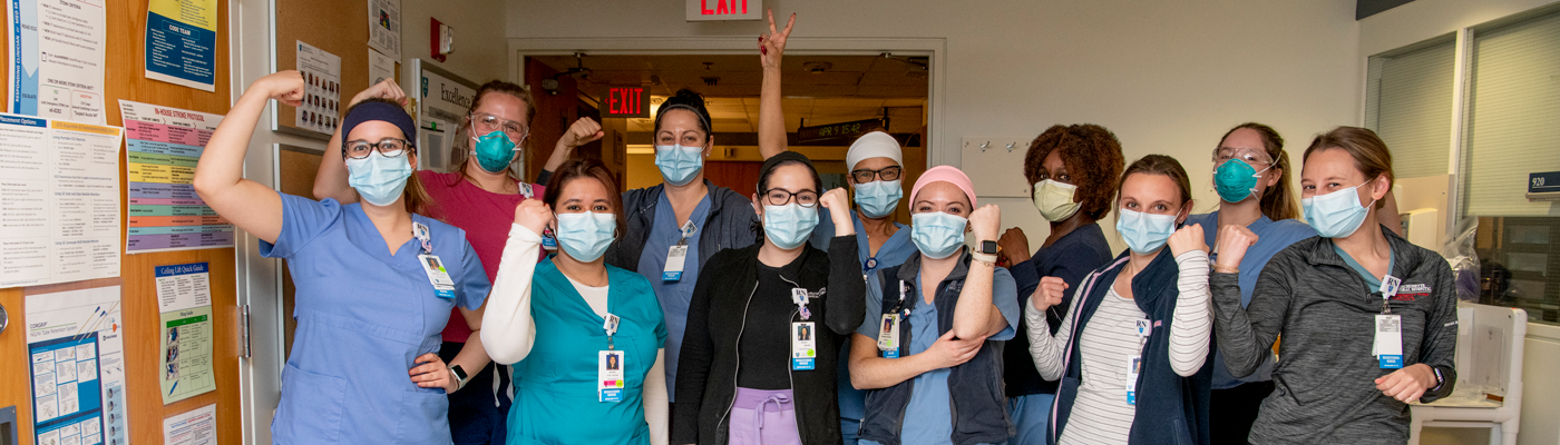 Masked nurses posing for picture in Mass General hallway