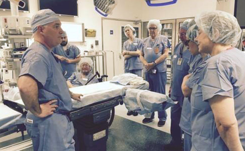 Peter Dunn, MD (left), executive medical director, Perioperative Administration, gives General Patient and Family Advisory Council members a tour of a procedure room.