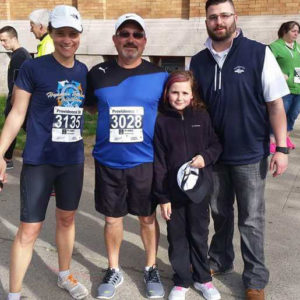 After finishing the SMART program, Mr. Cabral ran in a 5K race. He is flanked to the left by his physical therapist, Gwen Larsen, who ran with him, and his children, Arianna, and Aaron.