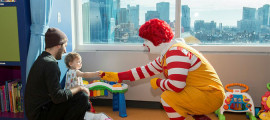 Ronald McDonald entertains Alex Arroyo (16 months) and his dad, Adam, in the beautiful new MGHfC playroom.