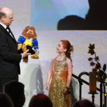 MGHfC Surgeon-in-Chief Allan Goldstein, MD, gifts patient Reese Robledo with a stuffed animal at the 2017 Storybook Ball.
