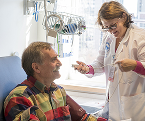 Clinical Research: Roberta Dee, RN, prepares patient Michael Bamber for an infusion of a new drug in a clinical trail TCRC.