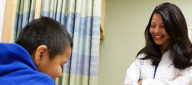 Elsie Taveras, MD, MPH (right), visits with a patient.