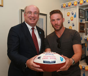 Wide receiver Julian Edelman, right, presented a special  commemorative ball to Dr. Slavin on behalf of The New England Patriots and the Kraft family.