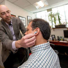 Vitaly Napadow, PhD (left), uses a prototype to demonstrate placement of his nerve stimulation device.