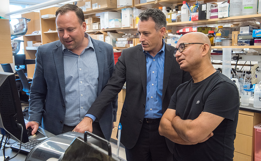 Mass General brain disease researchers (from the left) Stephen Haggarty, PhD, Roy Perlis, MD, and Rakesh Karmacharya, MD, PhD, confer about a cell model.