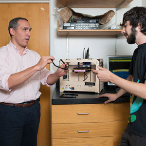 Sydney Cash, MD, PhD, holds a prototype of a device his lab is designing. Behind him, the 3D printing machine they use to create their designs.