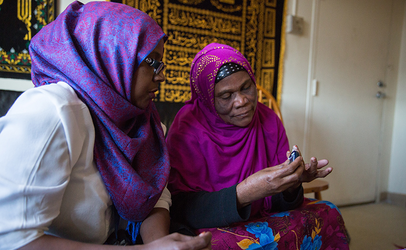 Community health worker, Kaftun Ahmed (left), checks in on a home visit with a refugee originally from Somalia.
