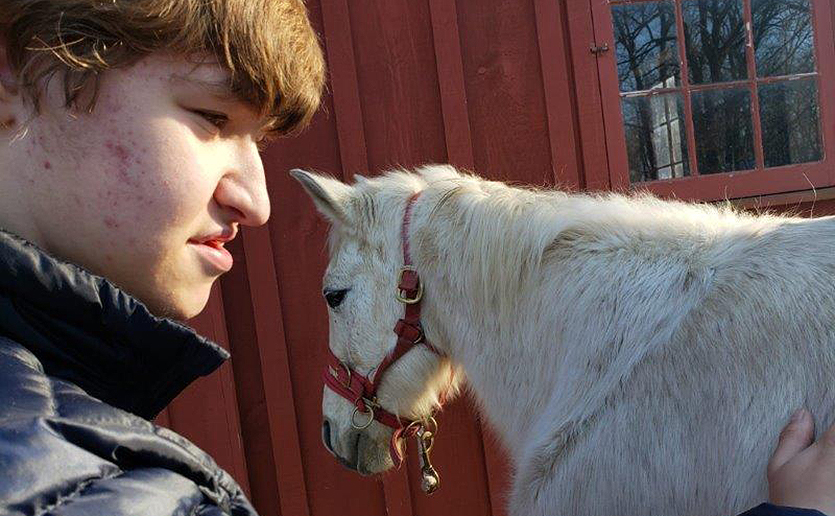 Since receiving care for a rare genetic disorder and enrolling in a private school, Jesse Simon has been deeply engaged in activities that range from classroom work to feeding horses in the school barn. (Photo courtesy of Monica Simon)