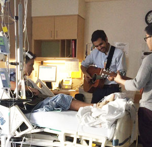 Josh Canales playing guitar with MGHfC music therapist Julio Gudino