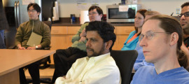 Mark J. Daly, PhD (right foreground), and Ramnik J. Xavier, MD (center), listen intently to a presentation in the Mass General Gastrointestinal Unit
