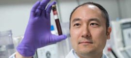 David Miyamoto, MD, PhD, a researcher in the field of early cancer detection, examines a blood sample.