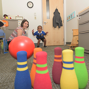 Therapist Jennifer Maietta uses low-tech toys to engage Kingston West and work on his language development.