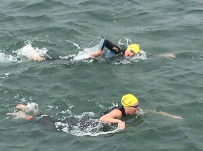 Swimmers brave chilly waters in the Swim Across America Boston Harbor Islands Swim, which raises funds for pediatric cancer research.
