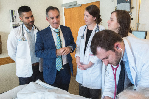 Alberto Puig, MD, PhD (second from left), director of the Core Educator Faculty Service at Mass General, confers with a group of medical students.
